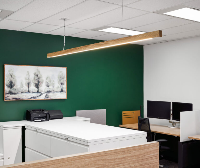Office filing area with forest green wall and suspended wood panelled strip light.