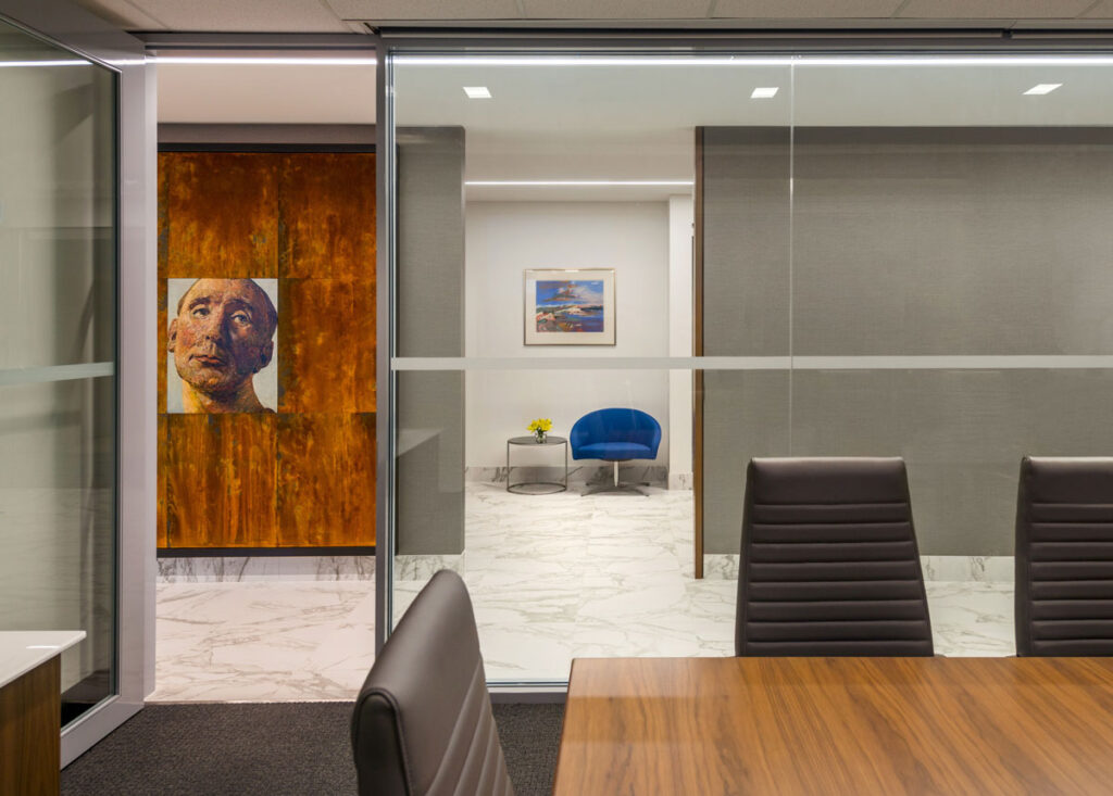 Glass walled meeting area with view to stone floor hallway, and wall with art piece.