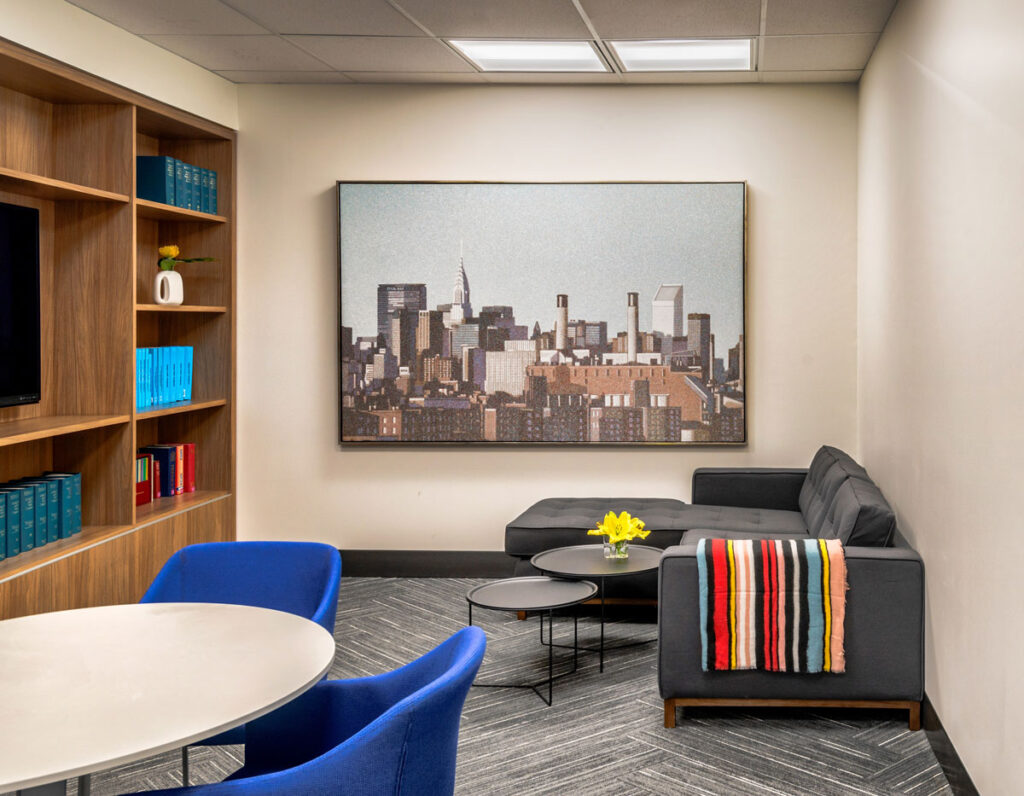 Office area with wood built-in bookshelves, round table with blue seating and dark gray sectional couch.
