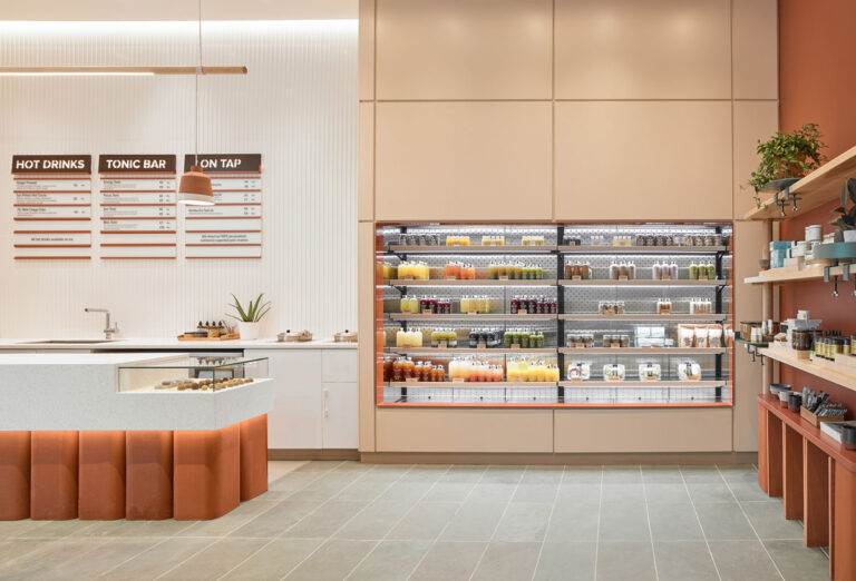 Open fridges with juice products, terracotta coloured accent spaces.