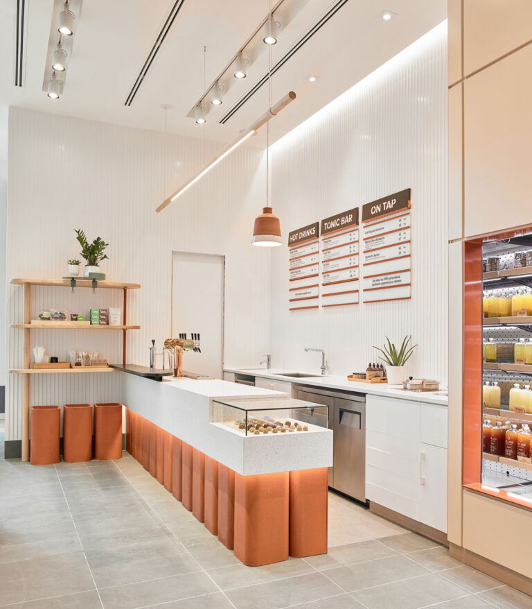 Juice shop with terracotta coloured stands and white walls.