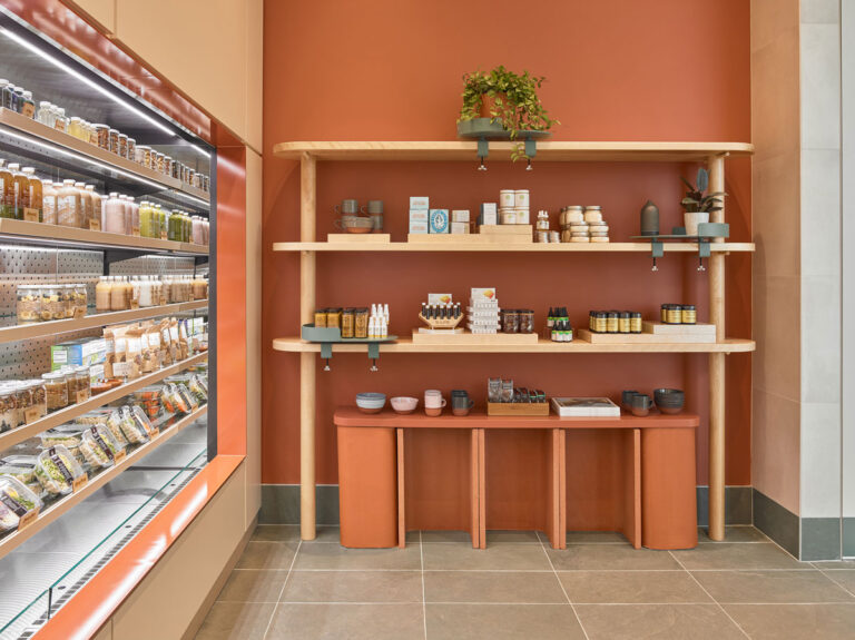 Open fridges at juice bar, next to open shelving on terracotta painted wall with products on wooden shelving.