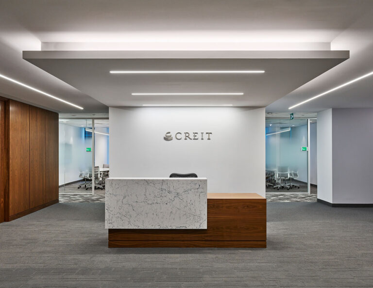 Reception area at CREIT with gray carpeting wood reception desk with white marble accent and ceiling accent.