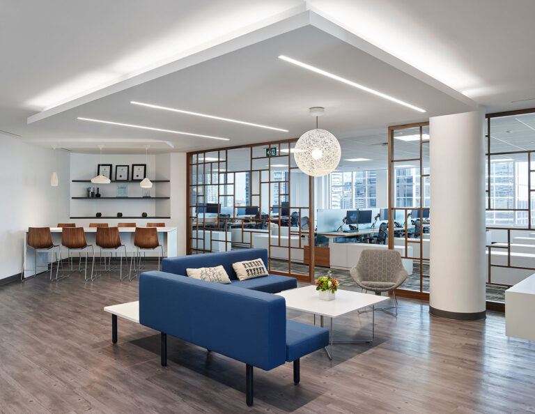 Lounge space in open concept office with glass wall trimmed in mable, 8 seater high top and blue and gray couch area.