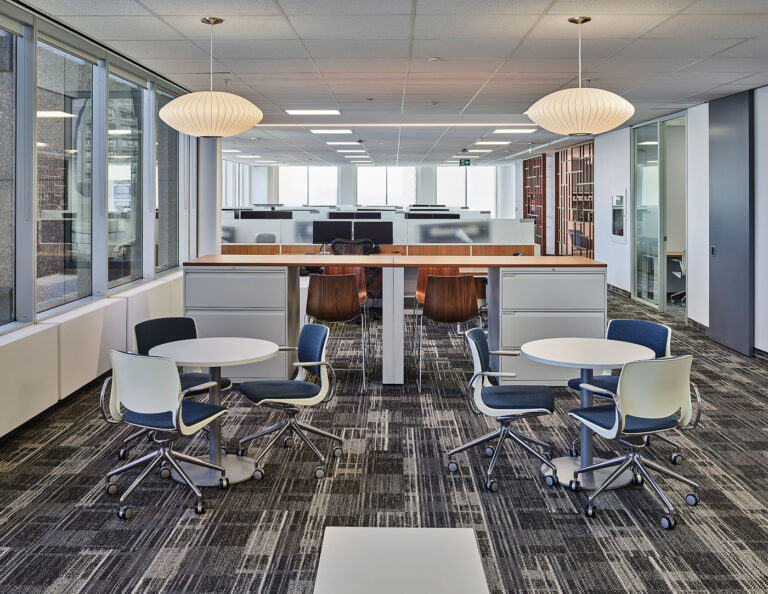 Open concept office space area with desks, wood topped high top area and ptterned gray and white carpet with