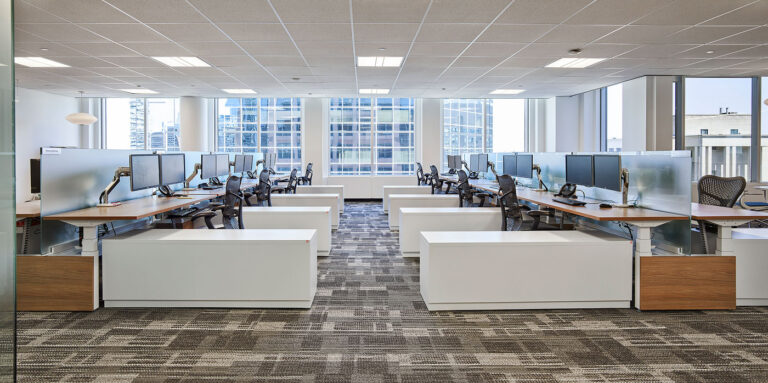 Open concept workspace with sets of desks, glass desk dividers and low white filing cabinets.