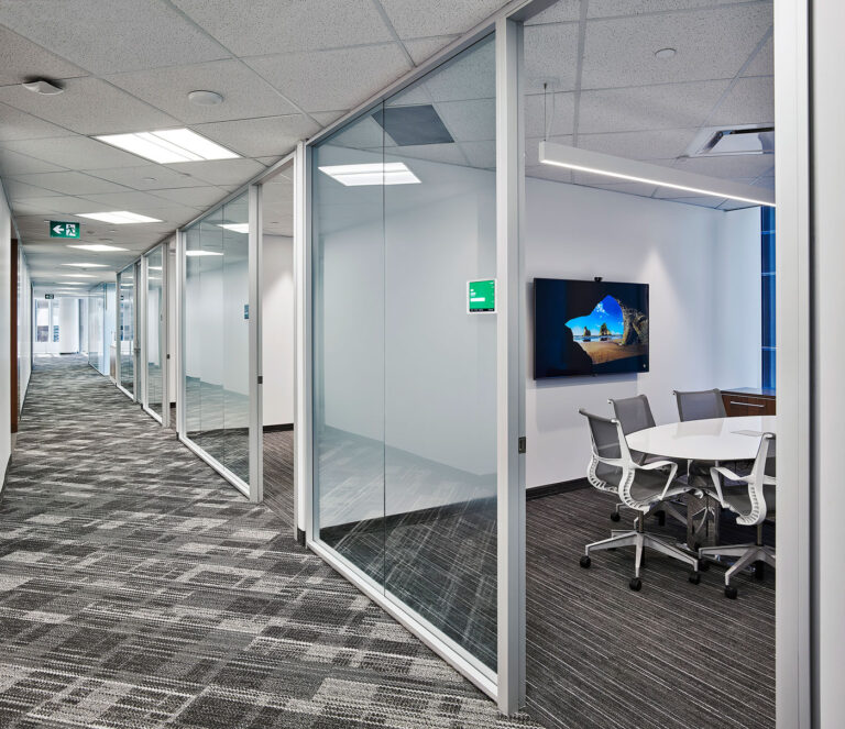 Corridor of glass walled private meeting areas with white walls and glass and white trim.