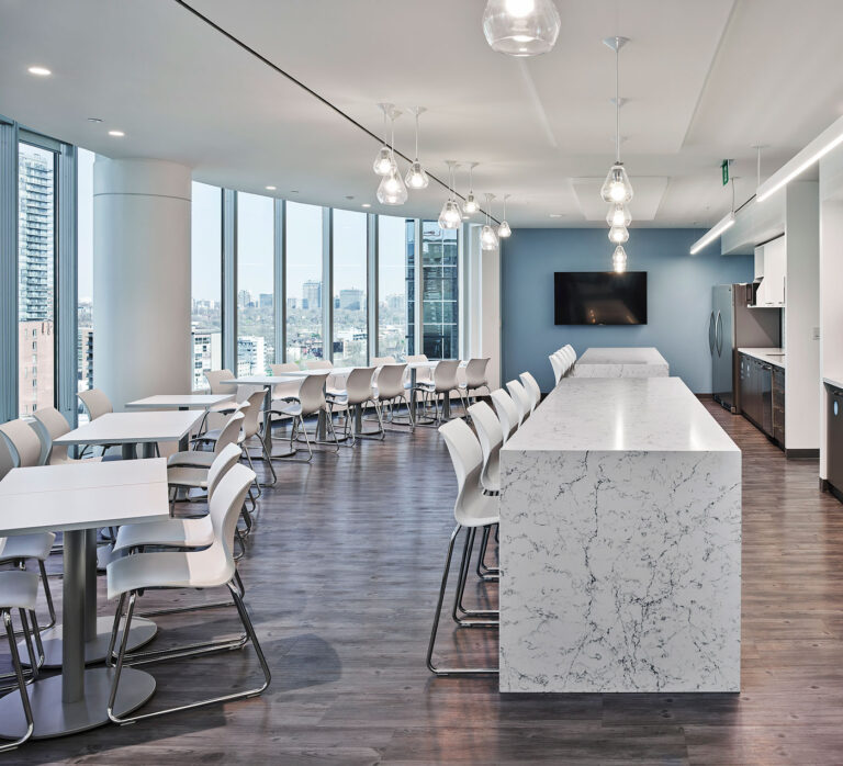 Cafeteria area with white seating and marble stand up islands.