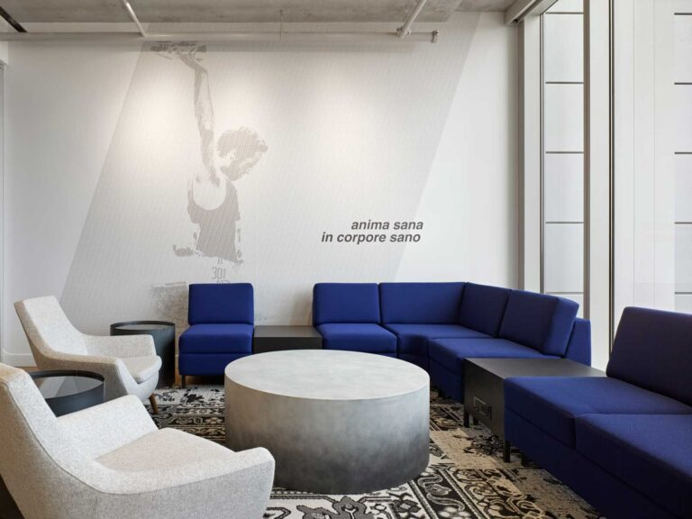White walled reception area at Asics Canada office with blue seating.