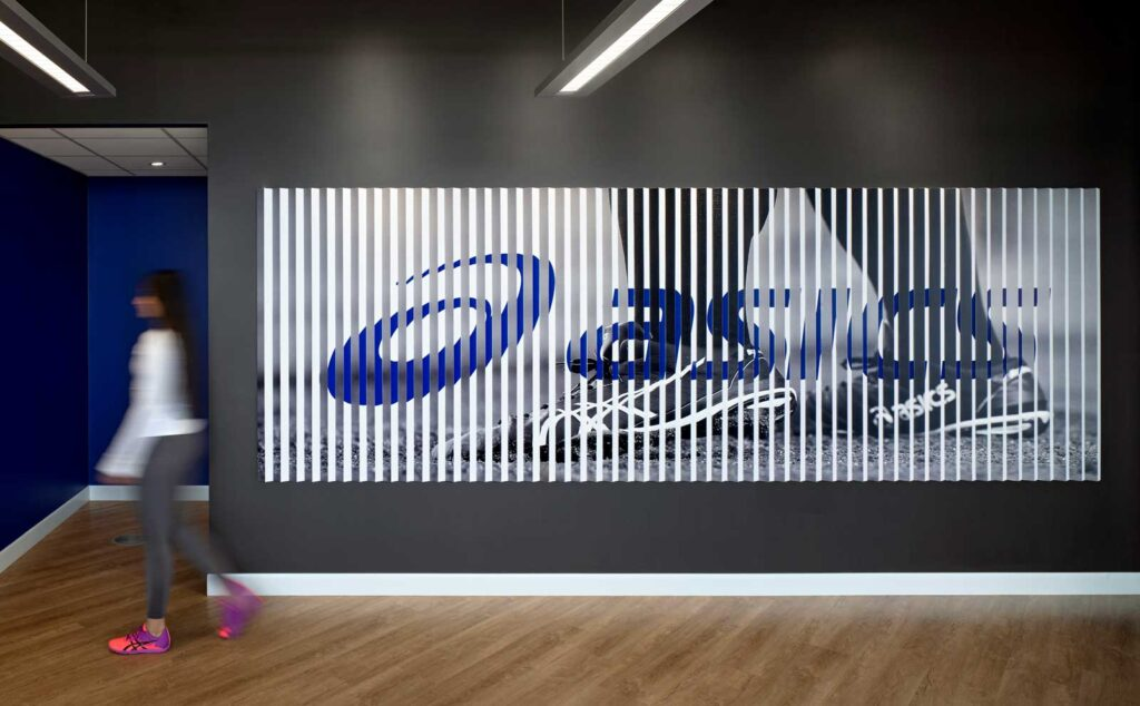 Blue and white lenticular wall with Asics company branding.