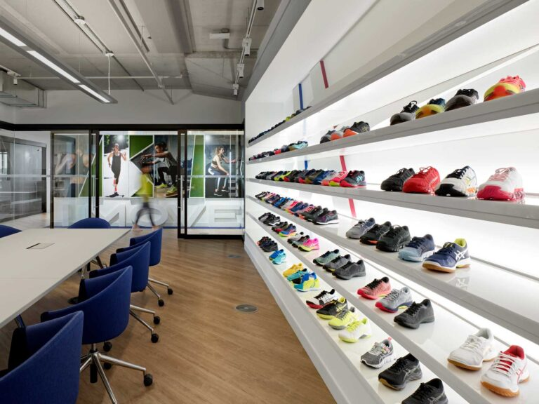 Boardroom with shelving of sneakers by Asics.