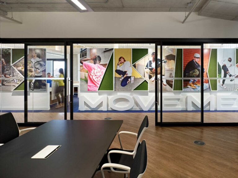 Boardroom with maple flooring with glass walls looking through to a wall of past asics ads.
