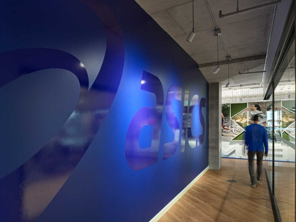 Matte blue wall with shiny asics branding graphic applied.