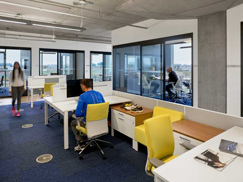 Office area with white desks and yellow seating.