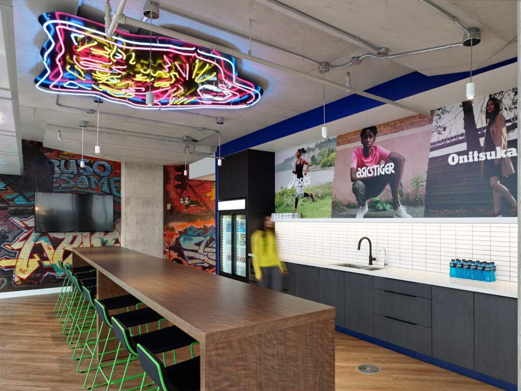 Cafeteria area at asics Canada with neon sculpture on ceiling, and a wood panelled island with lime green metal stools.