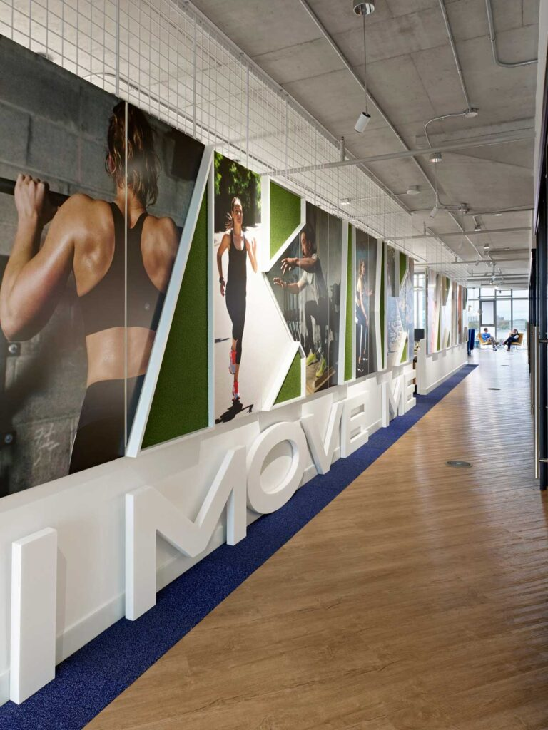 Wall with 'Movement' sculpture underneath images of people working out.