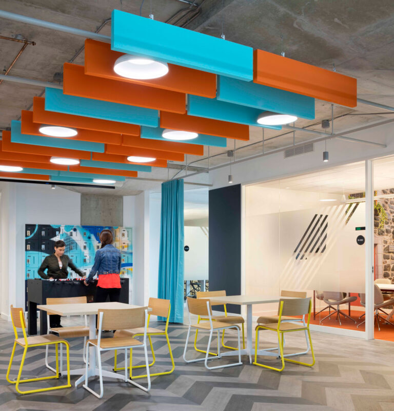 Casual meeting area with orange and blue acoustical panelling on a concrete ceiling.