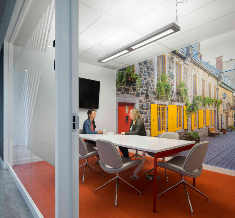 Private meeting room with wall graphic of Amsterdam street scene and red flooring.