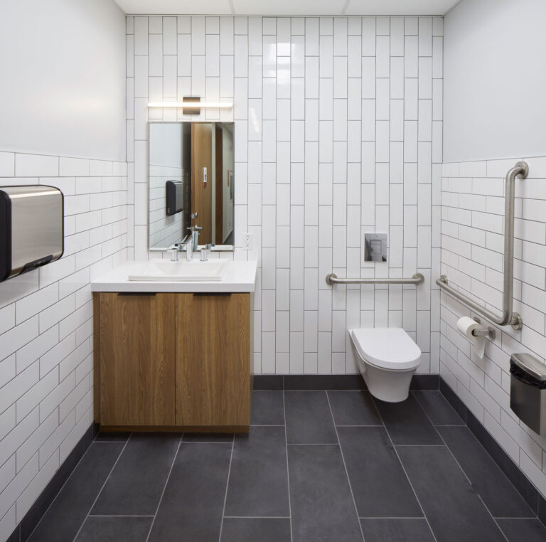 Bathroom area with gray tile, white subway tile walls and a white and wood laminate sink.
