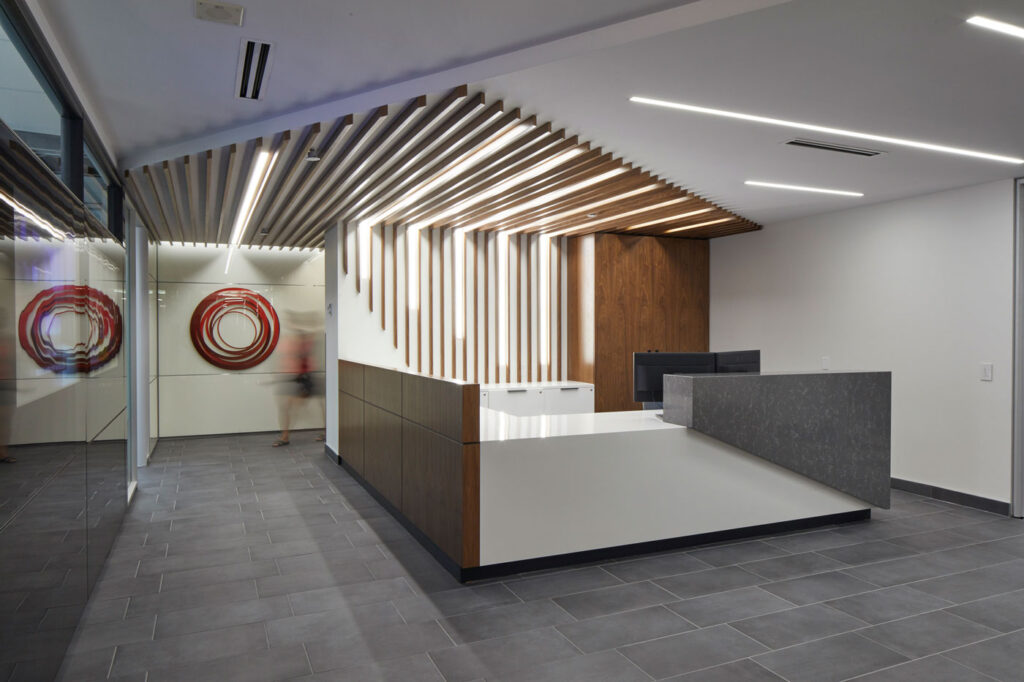 Reception area with gray tile flooring, and sculptural reception desk with wood and marble accents.