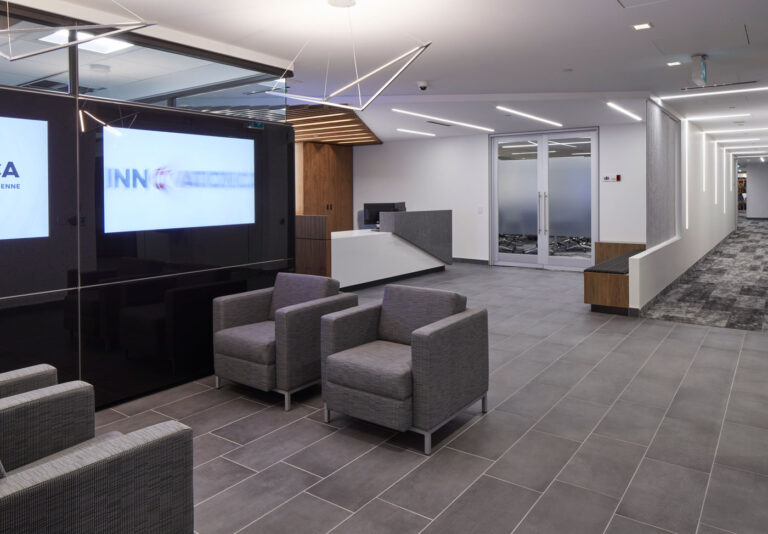 Seating at reception area with gray tile flooring, tv screens and sculptiral florescent lights.