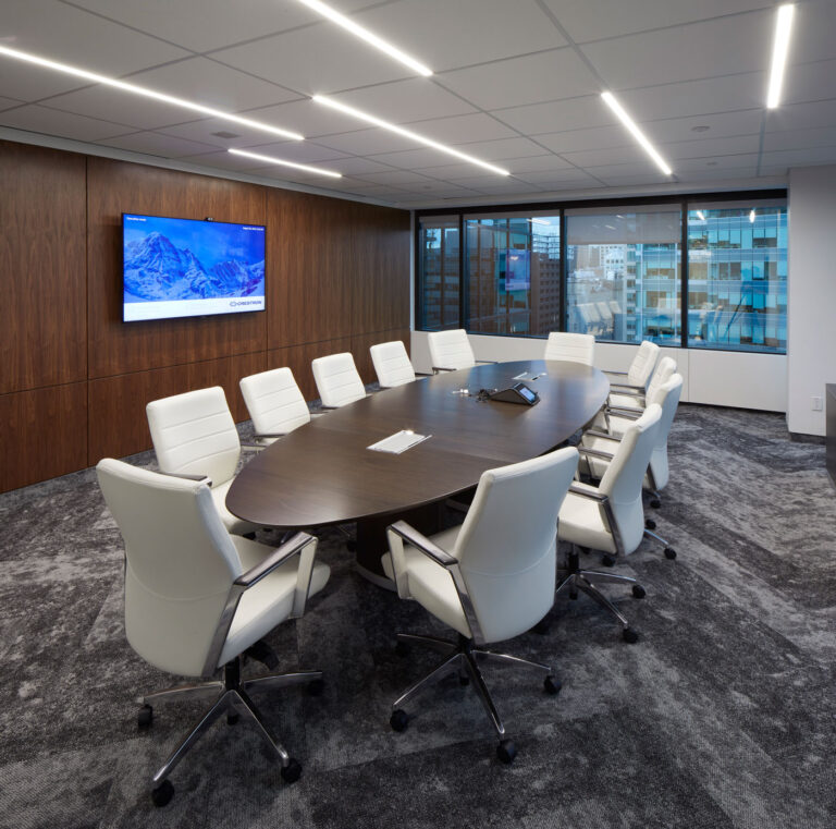 Boardroom with gray textured carpeting, long wood wall and oval shaped boardroom table with white rolling chairs.