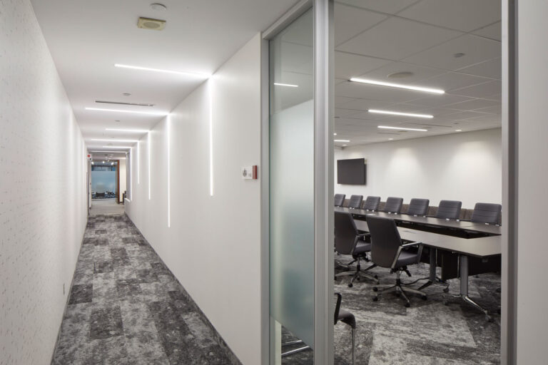 Hallway with gray carpeting and white walls, which looks into a large boardroom with gray seating, long rectangular tables.