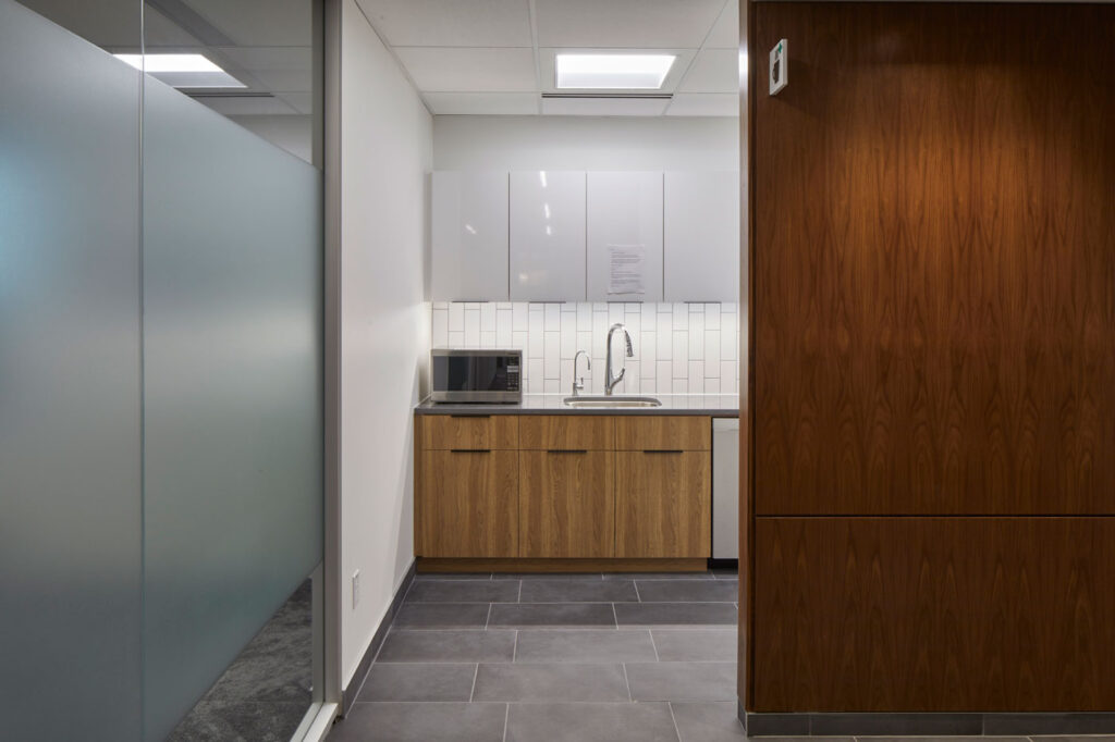 Kitchen area with white and wood laminate cabinetry and gray tile flooring.