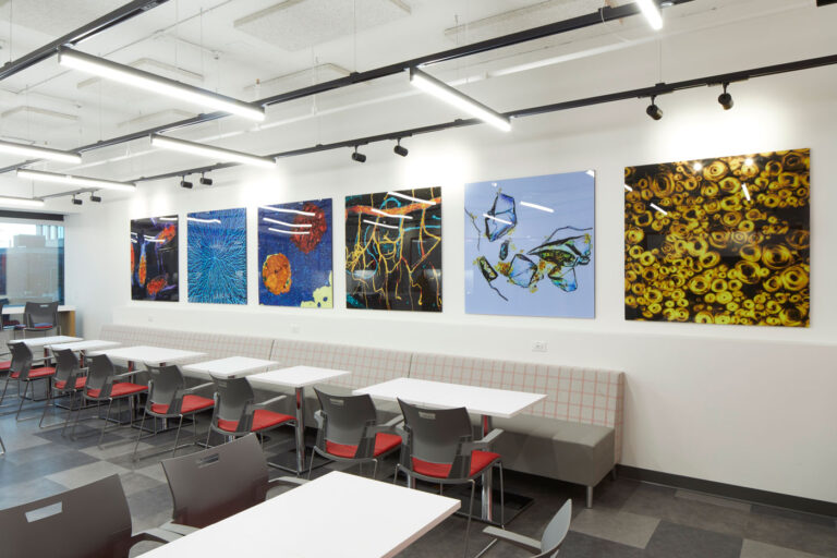 Lunch area with long bench and gray and red seating, glossy images of science and nature hang above to provide interest.