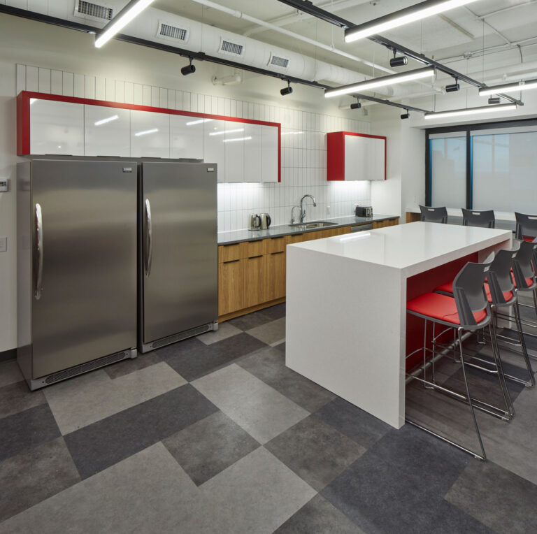 Kichen area with two stainless steel fridges, white stone island and red and white cabinetry.
