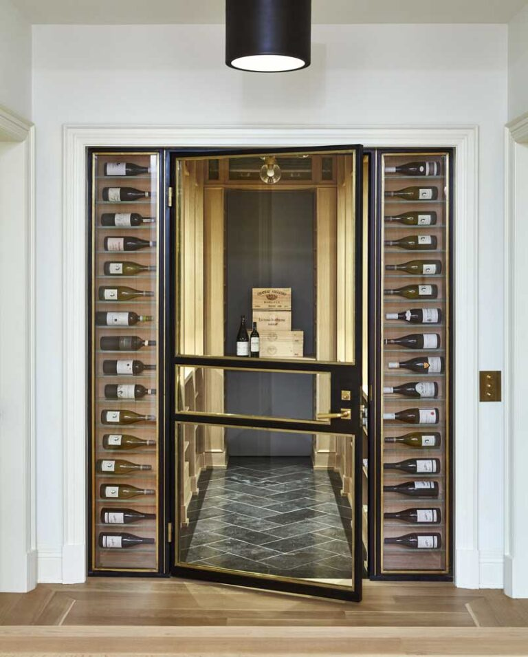 Wine cellar with large windowed door surrounded by bottles displayed on their sides.