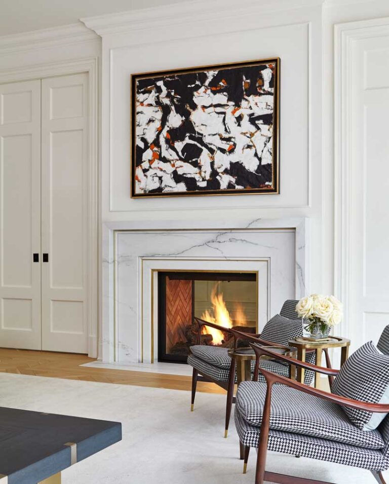 Detail of living room with two mid centutry modern chairs upholstered in black and white herringbone check and dark walnut arms, in front of a fireplace. A black and white painting hangs overhead.