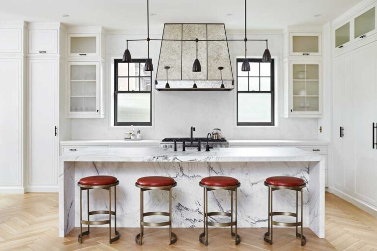 Kitchen with large waterfall marble island with white cabinetry and black accents. Four brass stools with red leather cushions are placed under the island.