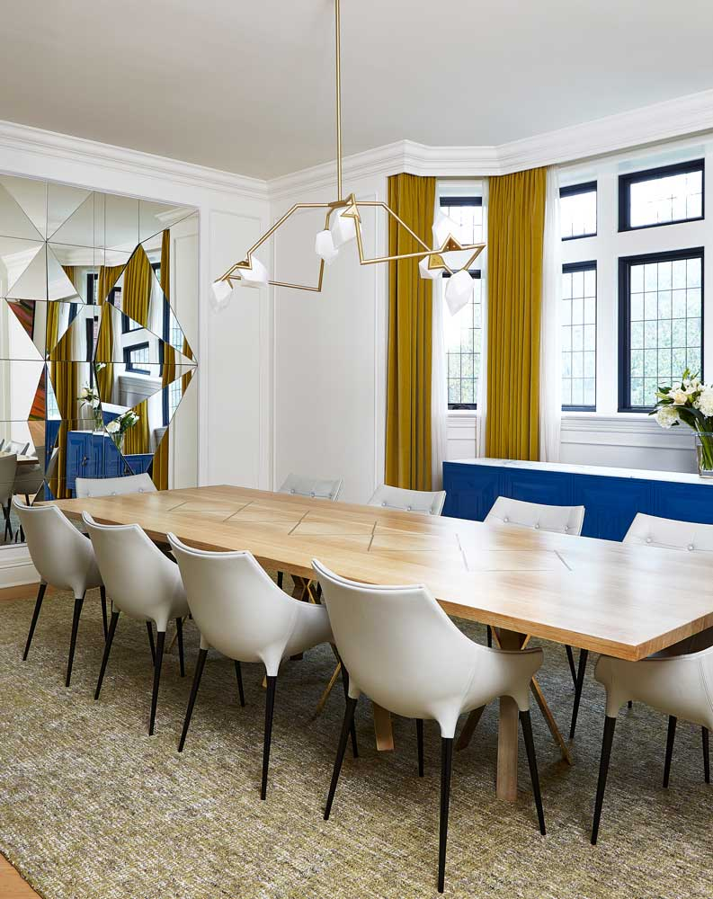 A long pale wood dining room table with 10 white chairs surrounding, a mirrored art piece at the head of the table reflects the room.