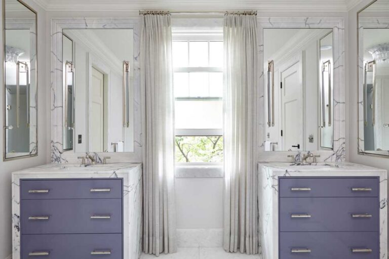 Bathroom with two sinks opposite a window with white and gray marble, and lavender blow drawers.