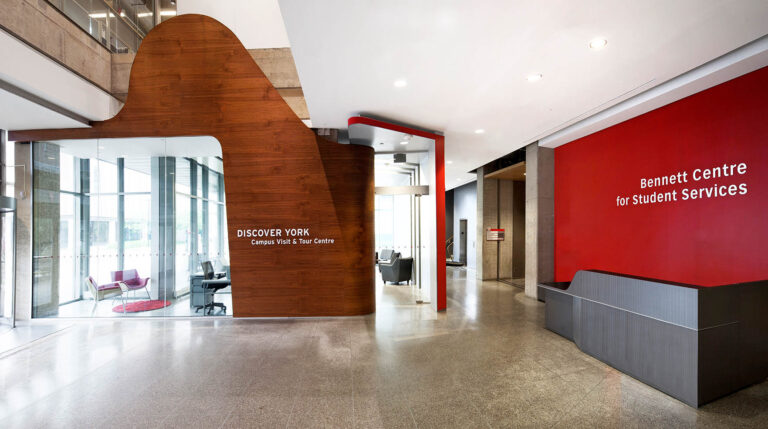 Entrance to Discover York with red accent wall and slate gray reception desk.