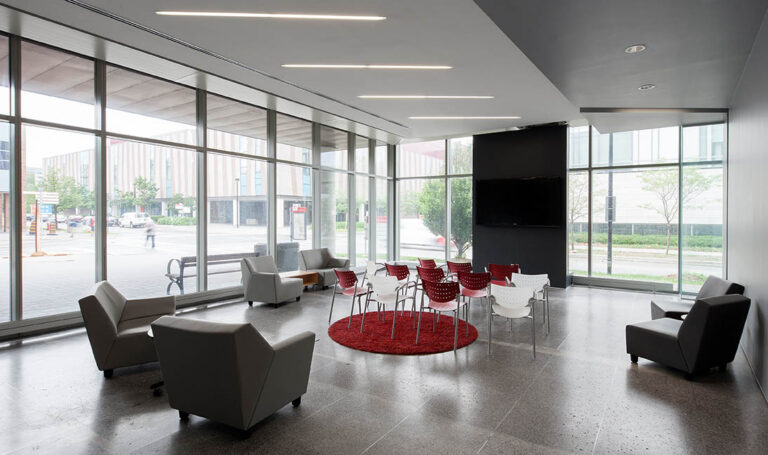 Seating area with polished concrete floor, wall of windows and red accent seating.