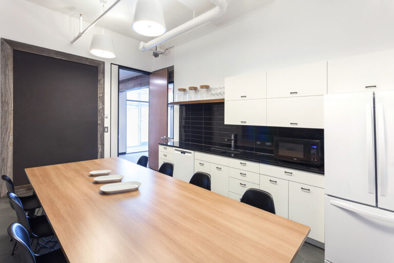 Kichen / break room area with sleek white walls and a large wood topped table.