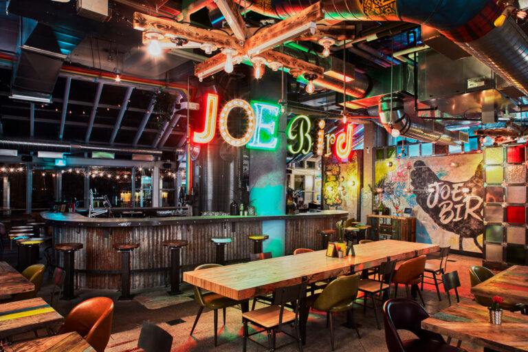 Interior view of Joe Bird restaurant with wood topped tables mismatched chairs, neon sign of restaurant name and open ductwork.