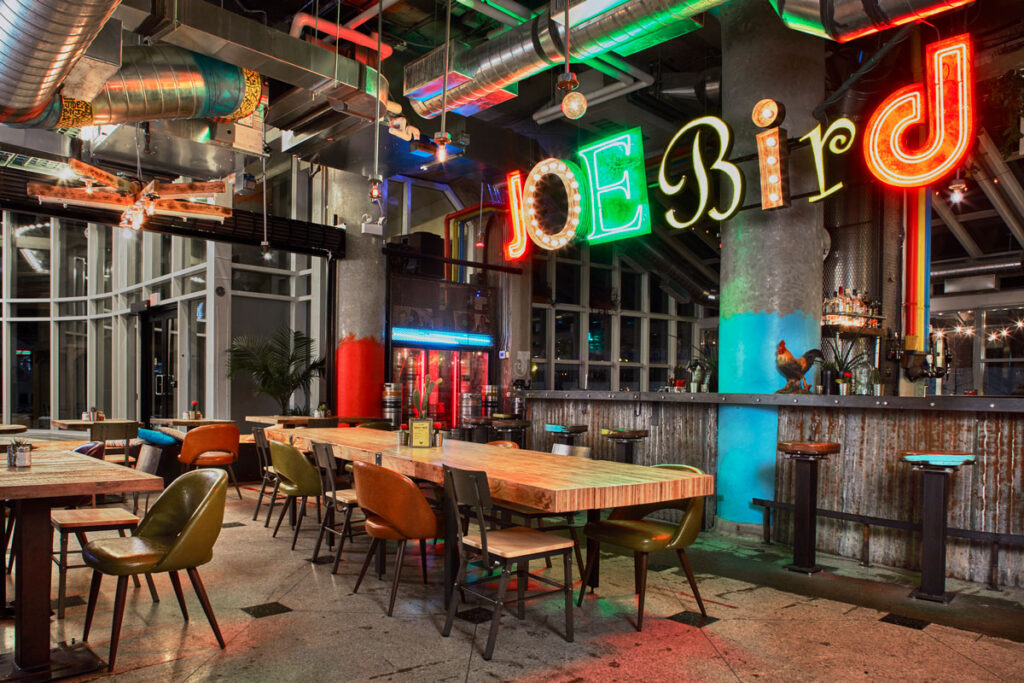 Dining and bar area of Joe Bird restaurant, with corrugated metal covering the bar and fixed stool seating.