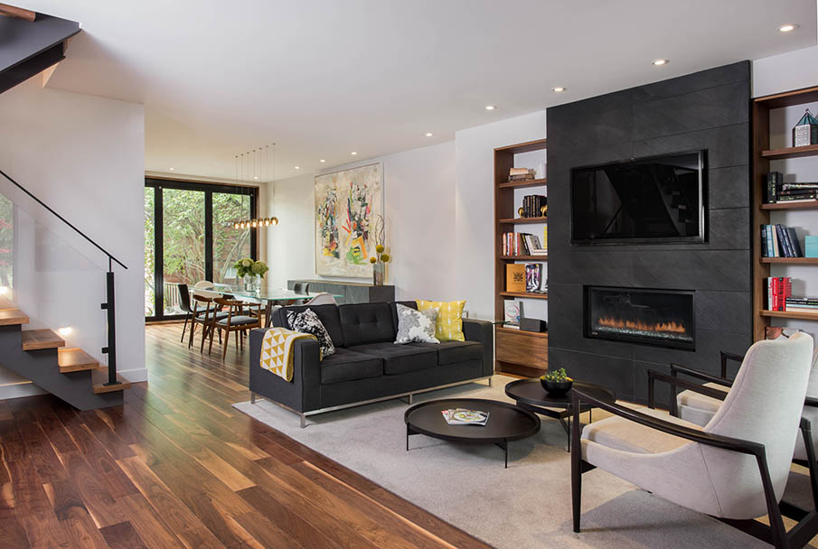Living room with white walls, hardwood floors, dark stone fireplace accent with TV inset and fireplace below.