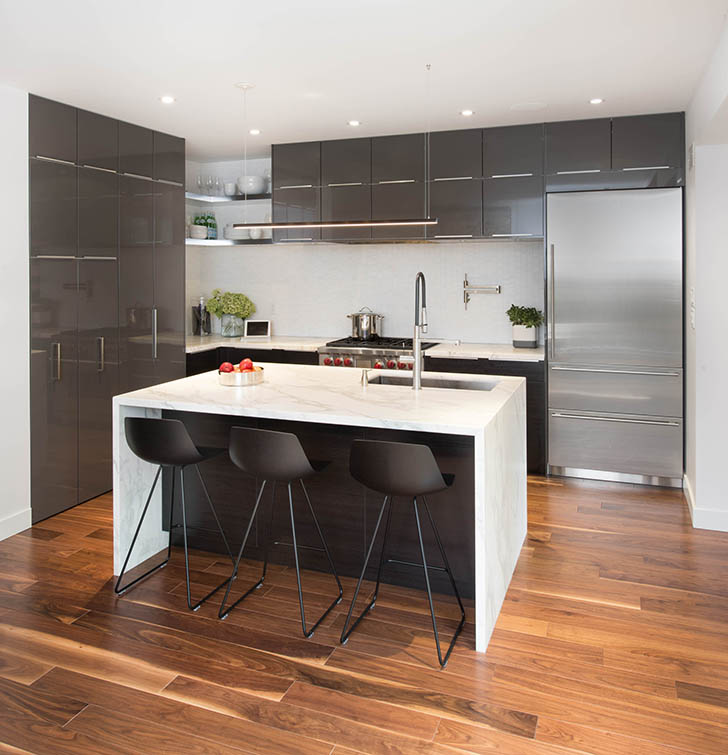 Modern kitchen with sleek gray cabinetry and white waterfall island, and stainless steel fridge.