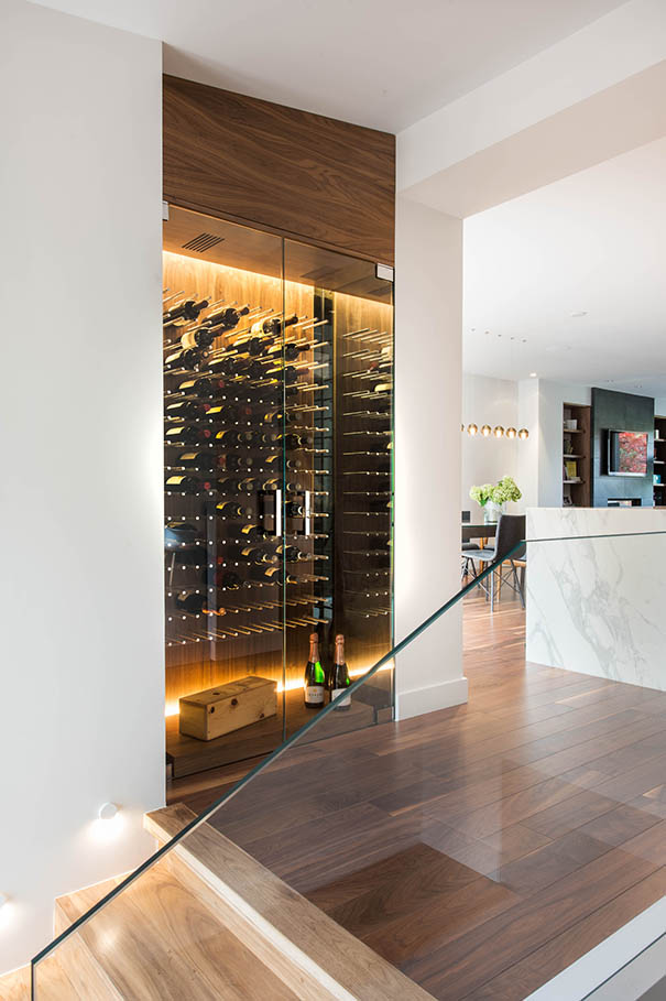 Wine storage area next to kitchen with glass wall and backlit wall.
