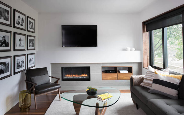 Lounge area with wood floor and large white rug, charcoal sofa and accent chair. Gallery wall of photos opposite the windows.