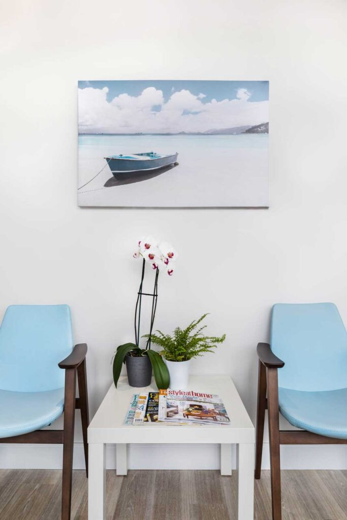A beach inspired waiting area with pale blue chairs and a photo of a beach scene hangs on the wall.
