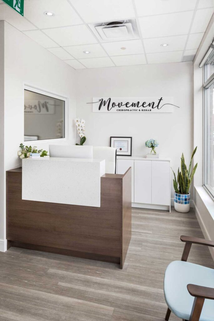 Reception area at Movement Chiropractic with white walls and a wood lined reception desk.