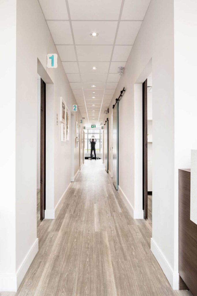 A long view down this chiropractic office hallway, with painted white walls and pale oak flooring.
