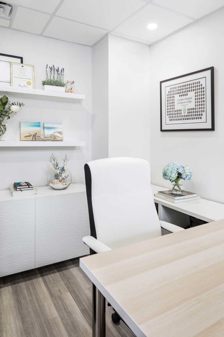 Clean white office area with floating shelves for degree and other photo frames.