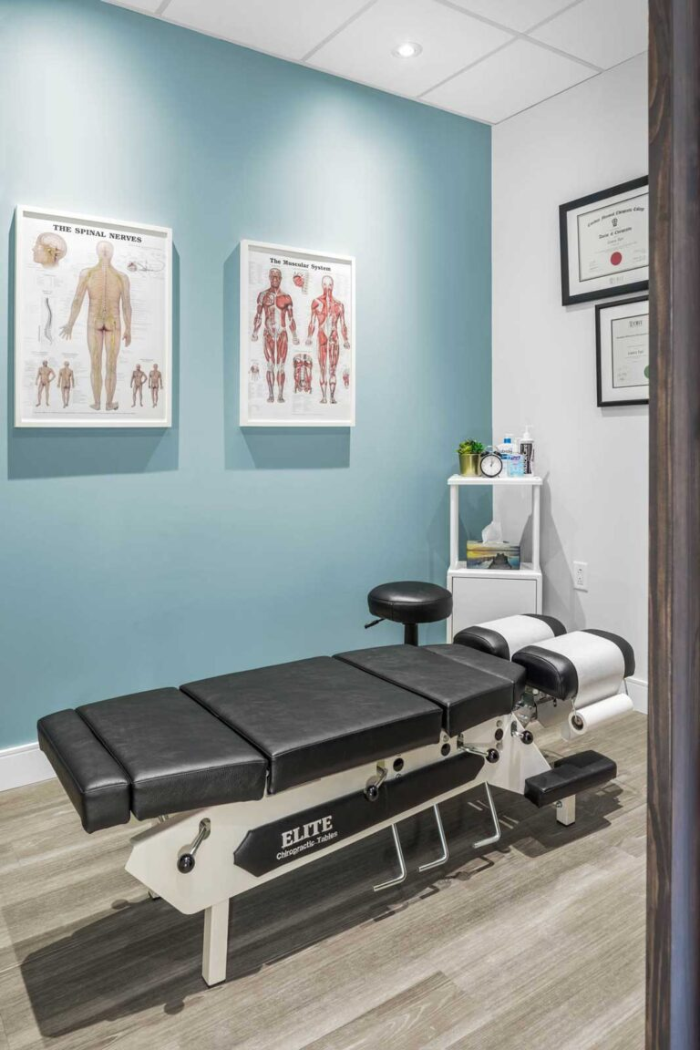 Private treatment room at chiropractice office with pale blue accent wall and anatomy diagrams on the floor.
