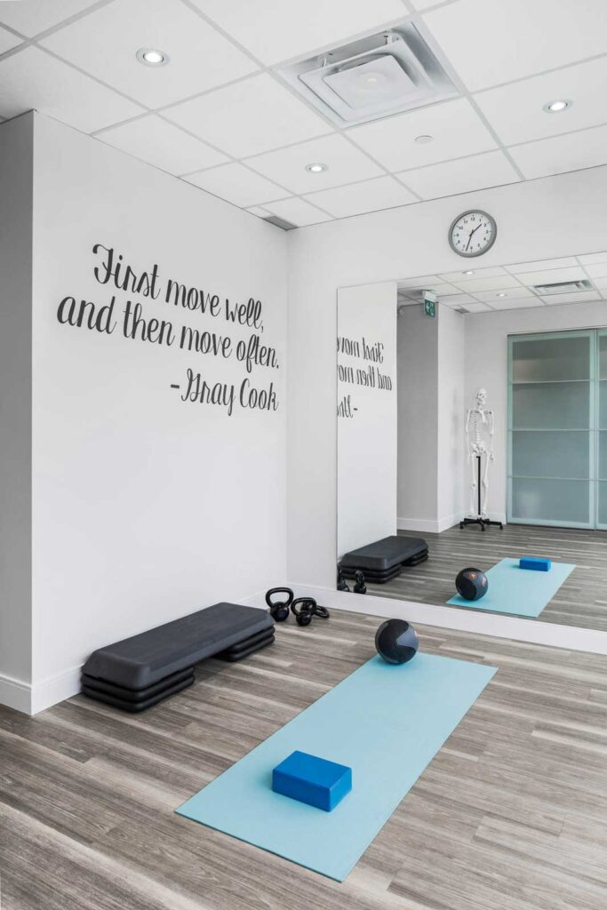 Open exercise area at chiropractic clinic with pale gray flooring and a quote 'First move well, then move often' on the wall.